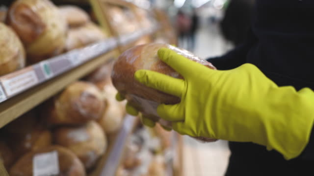 man in mask and rubber gloves choosing bread in a supermarket - glove stock videos & royalty-free footage