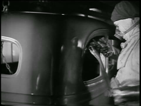 vidéos et rushes de b/w 1932 man in mask spray painting car body in ford car factory / industrial - ford