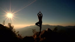 4K Man in meditation-Yoga position on the top of mountain at sunrise.