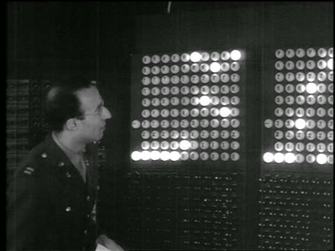 b/w 1946 man in military uniform standing next eniac computer as numbers light up / u of penn - 1940~1949年点の映像素材/bロール
