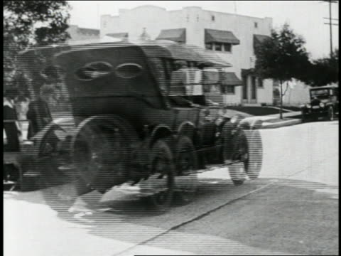 vídeos de stock, filmes e b-roll de b/w 1923 man (snub pollard) in mini-car with giant magnet being pulled along by passing car / feature - 1923