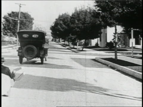 b/w 1923 rear view man (snub pollard) in mini-car with giant magnet being pulled by car ahead of it - 1923 stock videos & royalty-free footage