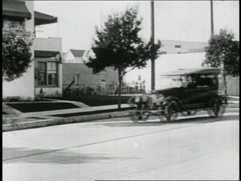 b/w 1923 man (snub pollard) in mini-car with giant magnet being pulled on street behind car / feature - 1923 stock videos & royalty-free footage