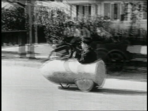 b/w 1923 man (snub pollard) in mini-car with giant magnet moving down street / feature - 1923 stock videos & royalty-free footage