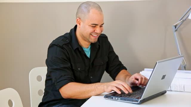 vídeos de stock, filmes e b-roll de man in modern office typing on laptop - careca