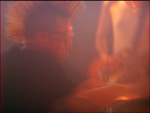 Man in mohawk + eyeglasses playing drums with man with spiked hair playing guitar in background