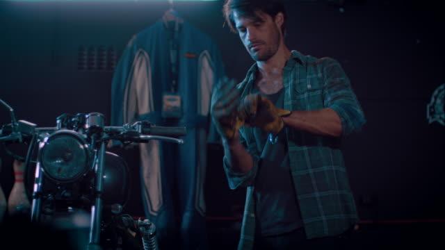 Man in motorcycle workshop grinding a piece of metal