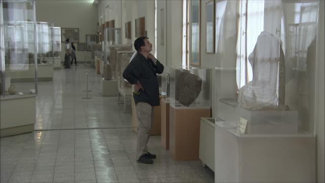 ws man in national museum of iran, tehran, iran - skåp med glasdörrar bildbanksvideor och videomaterial från bakom kulisserna