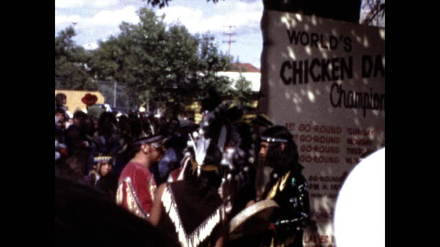 "man in native american headdress walking to the middle of the crowd with a microphone; little boy in native american clothing; sign ""chicken dance... - headdress stock videos & royalty-free footage"
