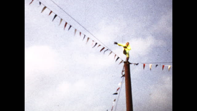 man in neon jacket climbing a tall pole while the crowd watches surrounding the pole; man reaches the top and does a headstand - rodeo stock videos & royalty-free footage