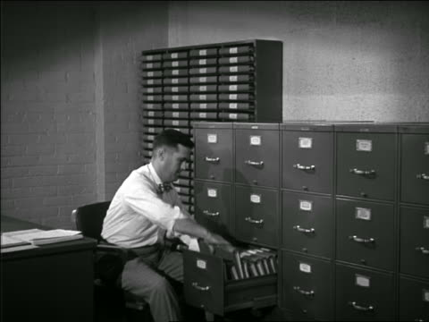 b/w 1949/50 man in office sitting in chair opening file cabinets + looking through book - filing cabinet stock videos & royalty-free footage
