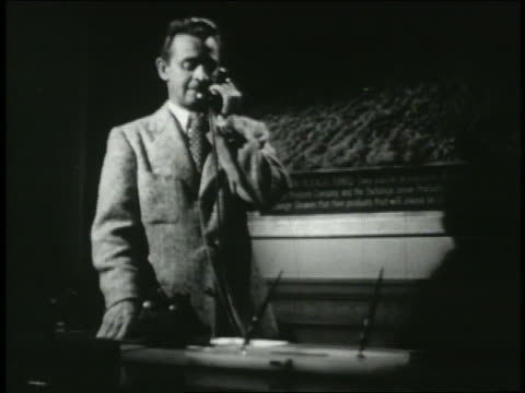 b/w 1949 man in office talking on telephone + hanging up - 1949 stock-videos und b-roll-filmmaterial