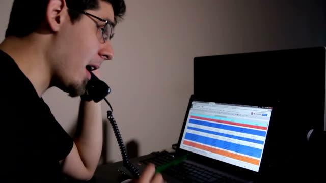 stockvideo's en b-roll-footage met man in office - working at a laptop - telefoonhoorn