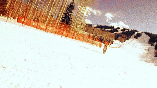 OVEREXPOSED PAN man in orange jumpsuit riding mountain bike in snow toward + past camera