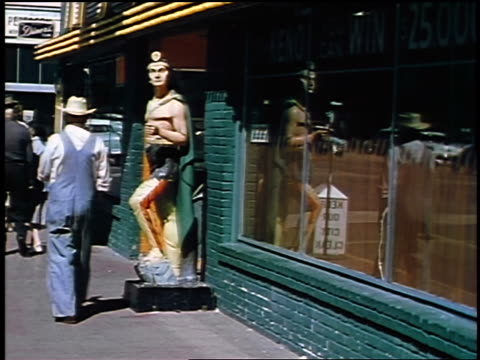 1957 rear view man in overalls + cowboy hat walking past native american statue on sidewalk - 1957 stock videos & royalty-free footage