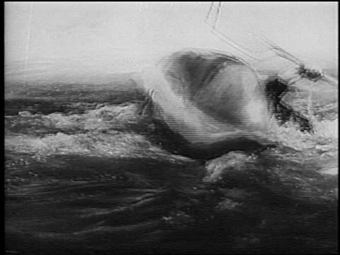 b/w 1966 man in overturned kayak righting self in slalom competition on rapids / germany / newsreel - 若い男性だけ点の映像素材/bロール