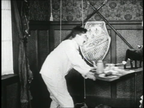 vídeos de stock e filmes b-roll de b/w 1923 man (snub pollard) in pajamas pulling cord + pants rise onto him / short - calçada