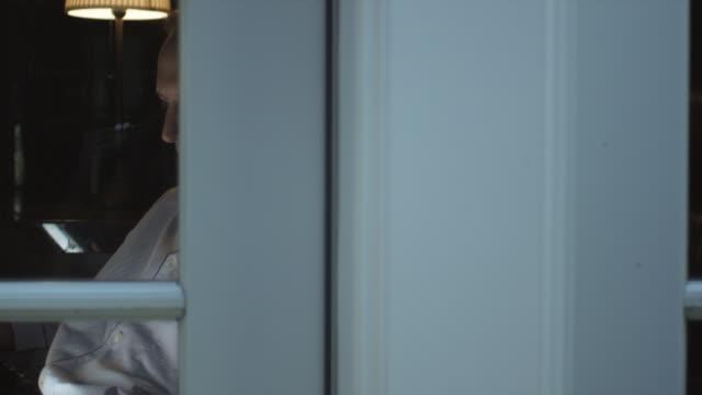 vidéos et rushes de pan, cu, man in pajamas reading at night, viewed through window - sitting