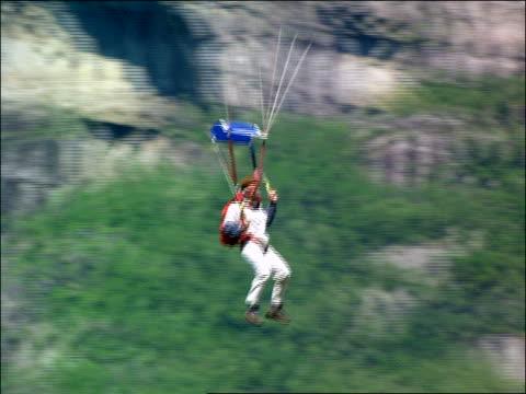 man in parachute landing safely on rocks / stavanger, norway - parachuting bildbanksvideor och videomaterial från bakom kulisserna