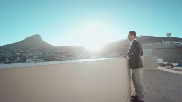 vídeos de stock, filmes e b-roll de homem na cobertura com vista para a cidade - telhado