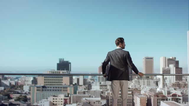 man in penthouse looking over the city - balcony stock videos & royalty-free footage