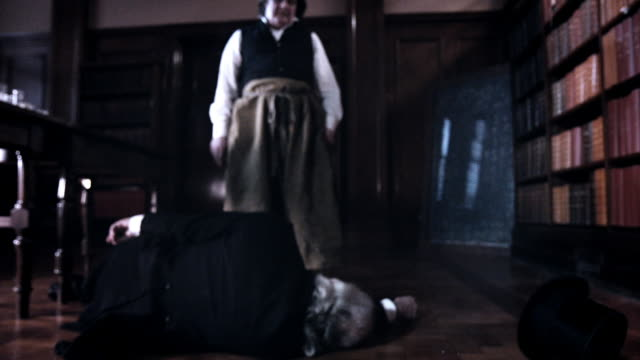 A man in period dress standing over the body pf another man, falls to his knees and holds his head in regret