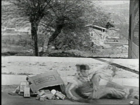b/w 1925 man in pile of boxes on street getting up + running offscreen / feature - 1925 stock videos & royalty-free footage