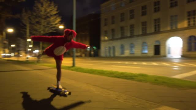 stockvideo's en b-roll-footage met man in pink rabbit suit rides skateboard in berlin at night - excentriek