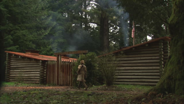 A man in pioneer clothing walks toward log cabins.