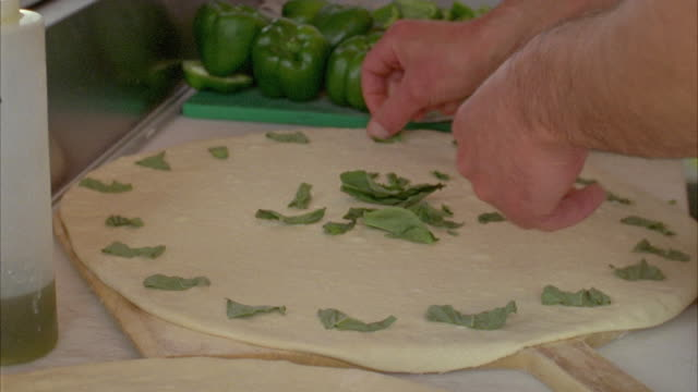 cu man in pizza shop positioning basil on newly pizza dough / marfa, texas, usa - basil stock videos and b-roll footage
