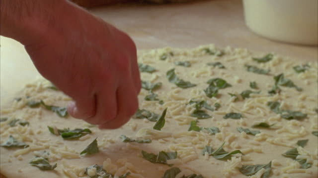 cu man in pizza shop sprinkling fresh mozzarella cheese on pizza dough / marfa, texas, usa - sprinkles stock videos and b-roll footage