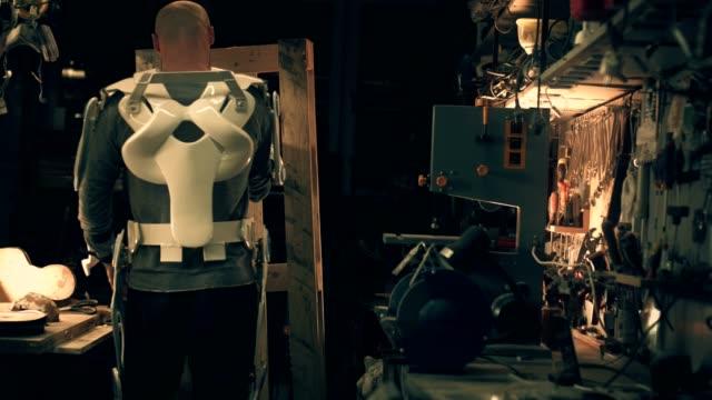 vídeos de stock, filmes e b-roll de homem em powered exoskeleton em oficina - carrying