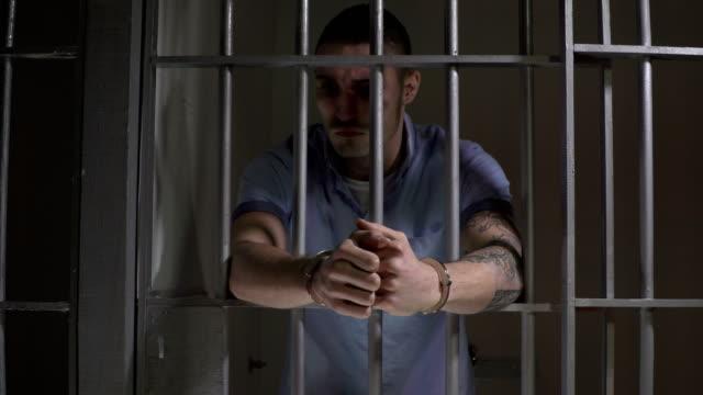 vídeos y material grabado en eventos de stock de 4k: hombre en celda de la cárcel con esposas - tire hacia atrás - preso