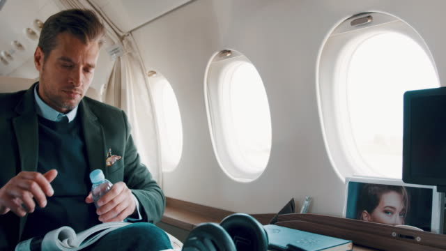 man in private jet airplane - water bottle stock videos & royalty-free footage