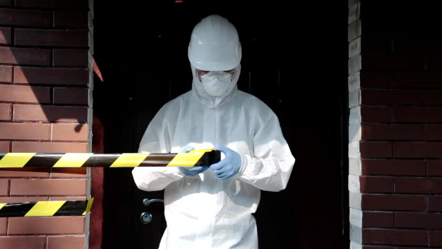 a man in protective clothing sets a warning tape in an infected area. - nuclear fallout stock videos & royalty-free footage