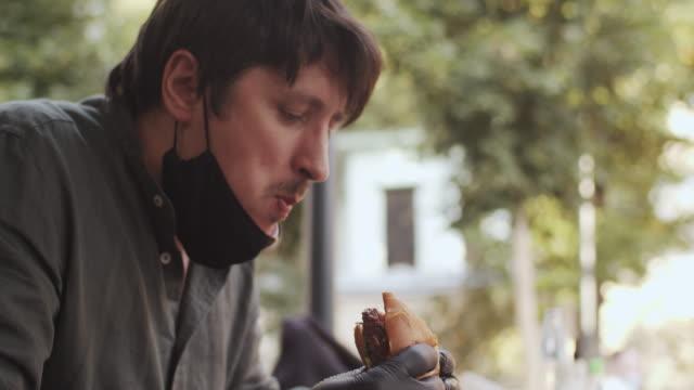 stockvideo's en b-roll-footage met mens in beschermend gezichtsmasker en handschoenen die hamburger in een koffie of een restaurant eten - fastfood