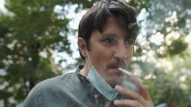 vidéos et rushes de homme dans le masque protecteur de visage fumant une cigarette - smoke physical structure