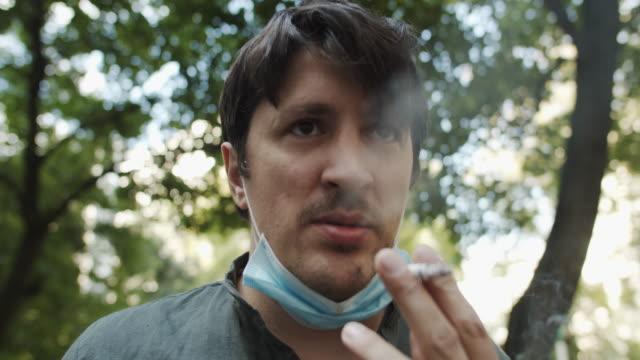 タバコを吸う保護フェイスマスクの男 - 紙巻煙草点の映像素材/bロール