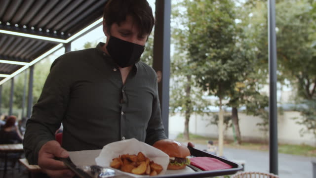 vídeos de stock e filmes b-roll de man in protective mask carrying tray with burger and french fries from a food-court or in a cafe - bandeja utensílio doméstico