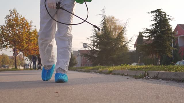 man in protective suit washing and disinfection sidewalk in residential neighborhood - full suit stock videos & royalty-free footage