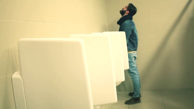 公衆トイレで男 - 小便器点の映像素材/bロール