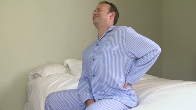 man in pyjamas with backache - backache stock videos and b-roll footage