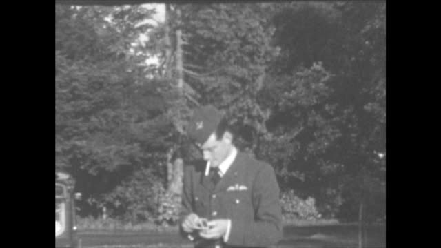 man in raf uniform, with cigarette: glimpse at beginning of car with a hood on a front light and white paint on the front of front wheel covers due... - white点の映像素材/bロール