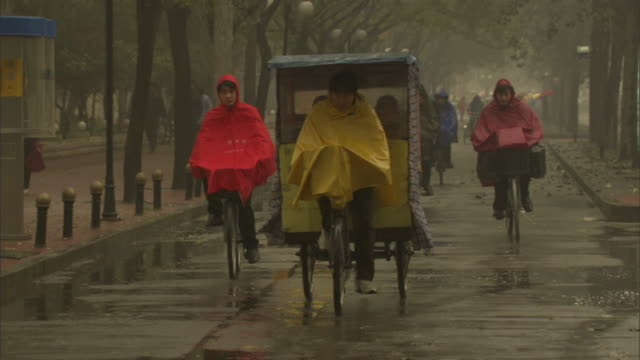slo mo ms man in rain poncho driving three-wheeled pedal taxi, other people riding bicycles in rain, beijing, china - waterproof clothing stock videos and b-roll footage