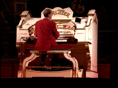 man in red coat playing wurlitzer organ on theatre stage - パイプオルガン点の映像素材/bロール