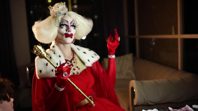 man in red dress with long fingernails sitting in dark room - drag queen stock videos and b-roll footage
