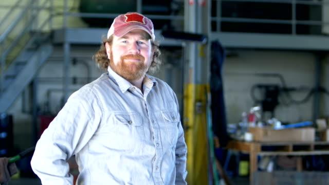 man in repair shop puts trucker's hat on head - trucker cap stock videos & royalty-free footage