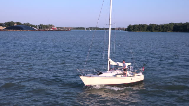 man in sailing boat at lake ontario in beautiful summer day nautical activities are a major recreational and tourist attraction in the canadian city - lake ontario bildbanksvideor och videomaterial från bakom kulisserna