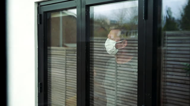 man in self isolation looking out of the window - sole video stock e b–roll
