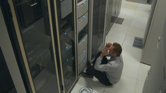ws man in server room sitting on floor, reeling back on floor, sydney, australia - netzwerkserver stock-videos und b-roll-filmmaterial